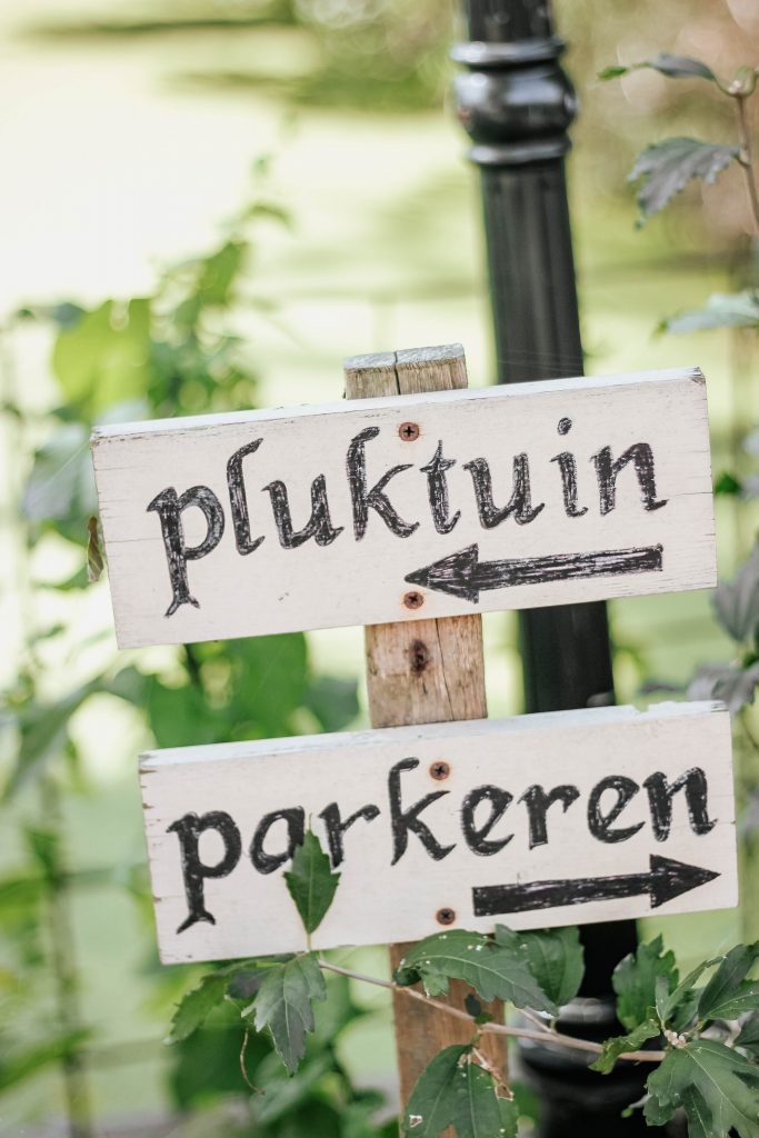 Dutch sign pointing left for pluktuin and right for perkeren