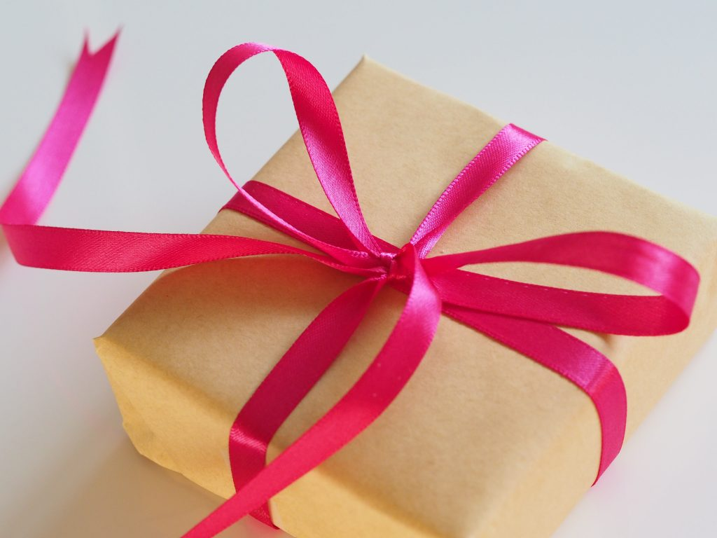 From Jess Bailey on Unsplash | Single gift wrapped in brown paper tied with bright pink ribbon