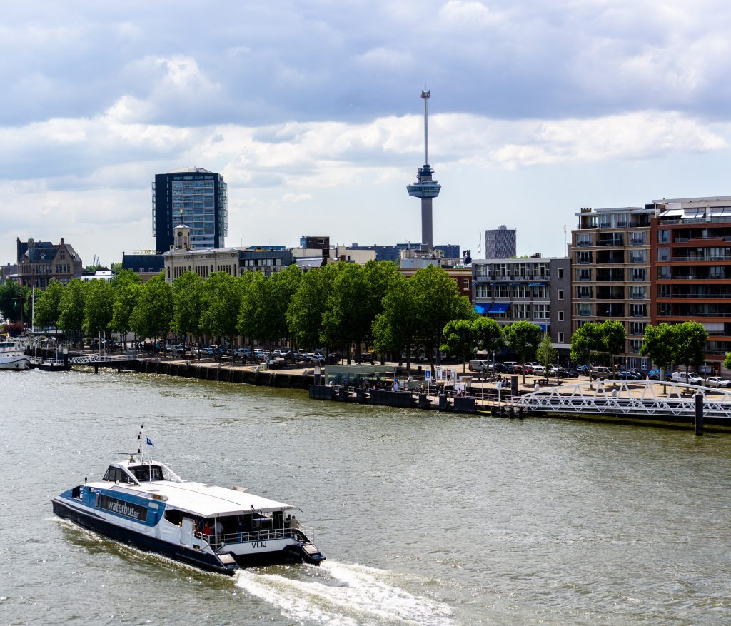 Euromast in Rotterdam with the river in the foreground and a boat passing through