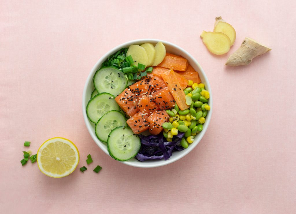 Poke bowl with salmon, cucumber, ginger, carrots and cabbage